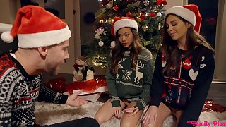 Two mouth watering girls are fucked hard by one lady's man under the Xmas three